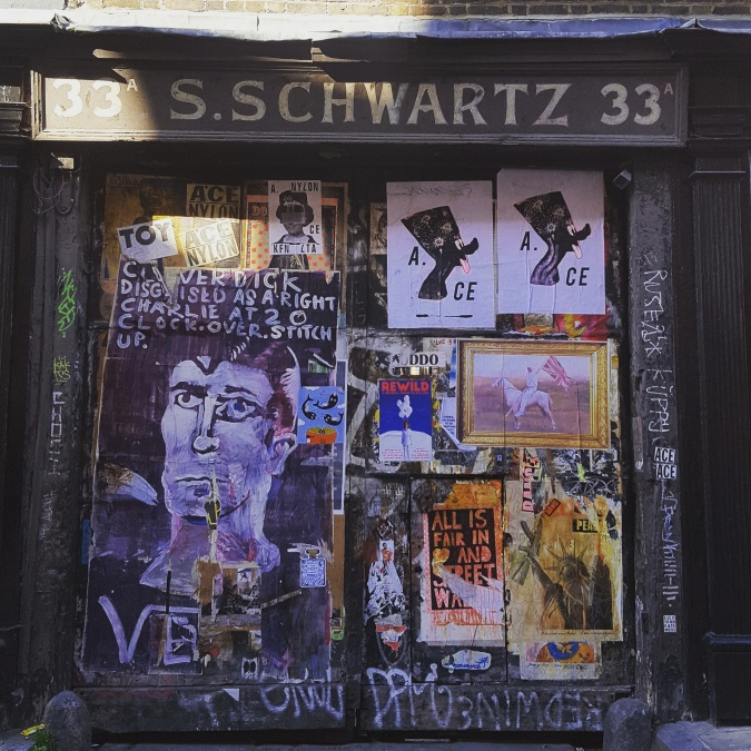 Posters and graffiti on a door in Fournier Street, Spitalfields