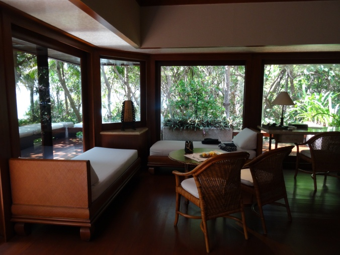 Seating area and indoor twin divans in a beach casita, Amanpulo